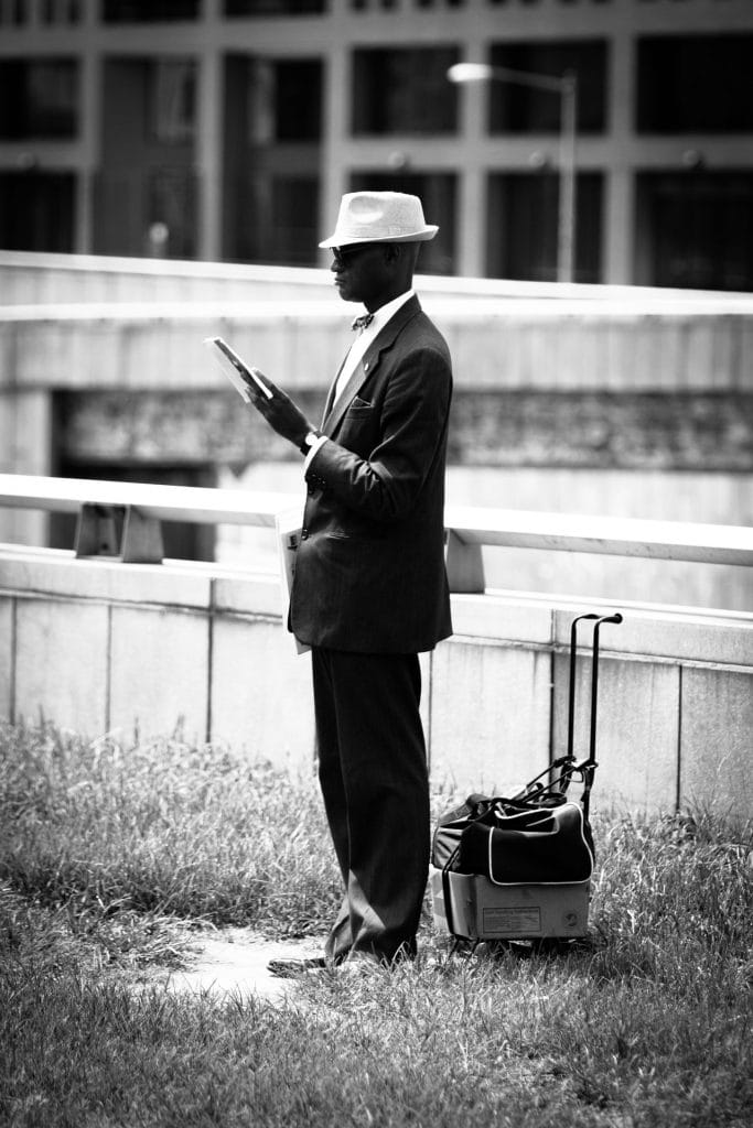A man with his newspaper | Daily Observations by Guillaume Groen | In Washington on the intersection of Massachusetts av and 2nd av was this man reading the newspaper that he is about to sell to passing cars.