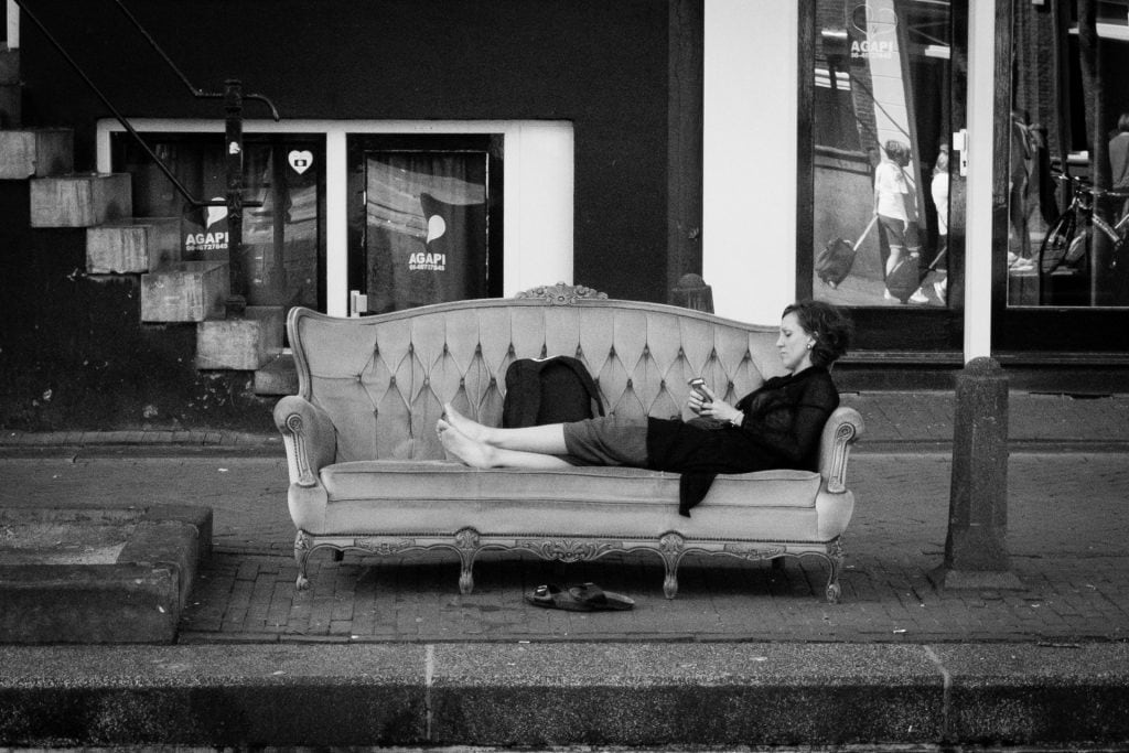 Resting on a bench along the canals of Amsterdam. Enjoying the heat disconnected from her surroundings. Daily Observations, 10-6-2017, Amsterdam, The Netherlands,