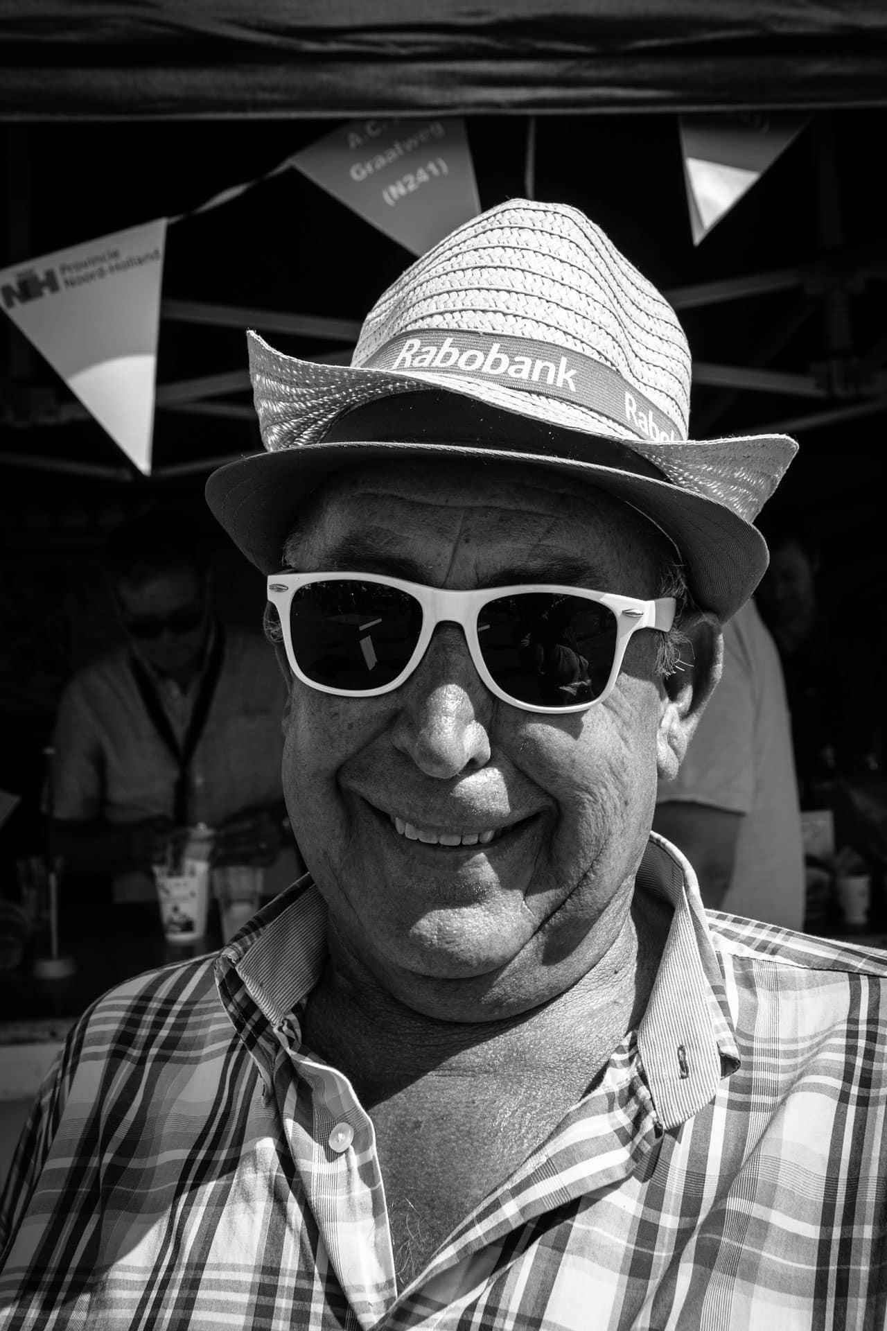 Walking around on the annual country fair (de landbouwtentoonstelling) in Opmeer this man received a hat from the Rabobank, A main local bank. and wore white sunglasses. 6-8-2018, Man with the white glasses #4, Opmeer, The Netherlands. As we street photographers roam the streets, observing and recording the fleeting moments that we encounter. Those Daily Observations go into photo books or as fine-prints on the wall as Street Photography grows as a profession and a medium.